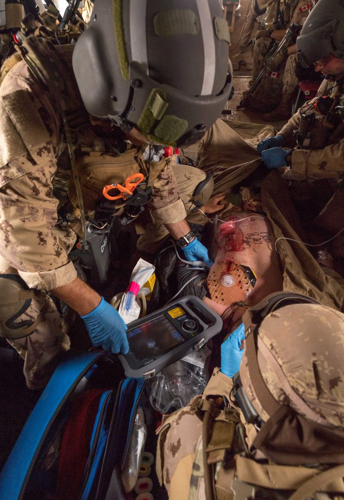 Members of the CH-147 Chinook medical team use a portable ultrasound machine on a simulated Dutch casualty