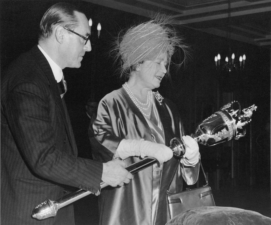 On December 3, 1963, Her Majesty Queen Elizabeth The Queen Mother inspected our new mace before it was shipped to Canada. She is with Sir Russell Brock, then president of the Royal College of Surgeons of England.
