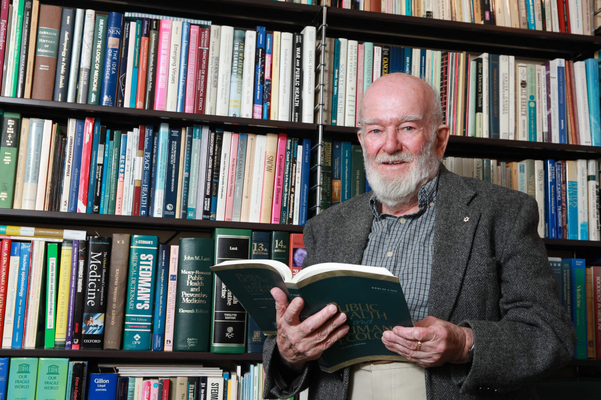John Last in January 2014, holding his book Public Health and Human Ecology (New York: McGraw Hill, 1997). The bookshelves behind him to his right hold many books that he wrote or edited, or to which he contributed chapters. Photo credit: University of Ottawa